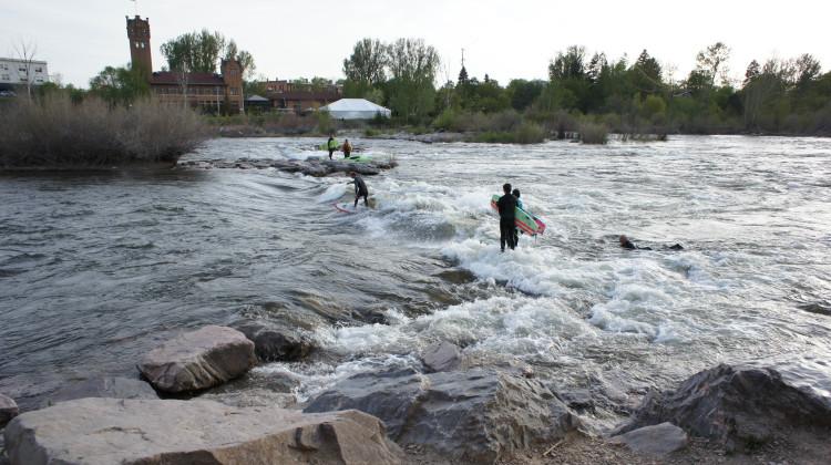 Surfers riding river waves downtown Missoula, Montana